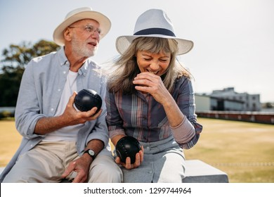 Senior woman in hat laughing while sitting in a park with a senior man. Senior couple enjoying their time sitting on a bench outdoors holding boules.