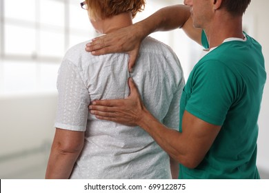 Senior woman having chiropractic back adjustment. Osteopathy, Alternative medicine, pain relief concept. Physiotherapy, sport injury rehabilitation
