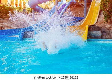 Senior woman having fun on water slide in hotel aquapark. Summer vacation