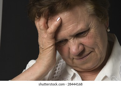 Senior woman having headache on dark background