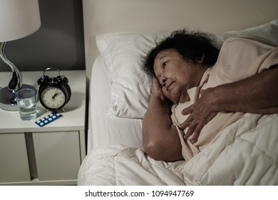 senior woman having heart problem in a bed at night