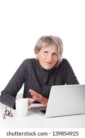 Senior woman having trouble with her computer shrugging her shoulders and looking to heaven for inspiration as she sits in front of her laptop