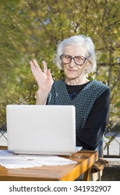 Senior woman having a video call on a notebook computer in the backyard