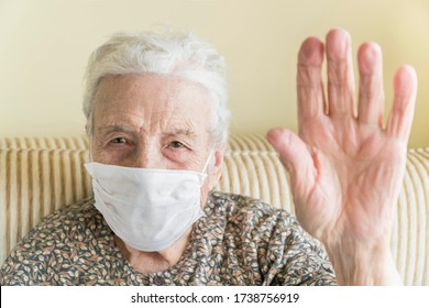 A senior woman with a health mask, making stop sign with her wrinkled hand. focus on the face