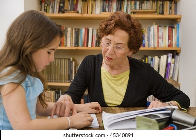 senior woman helping child doing homework