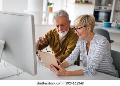 Senior woman helping senior man to use computer