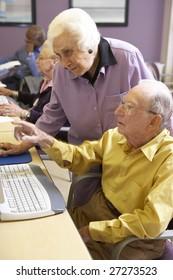 Senior woman helping senior man use computer