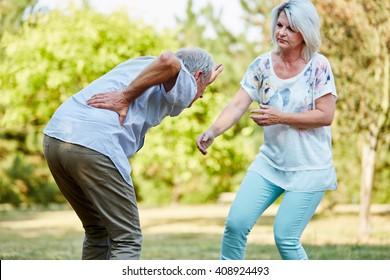 Senior woman helps man having lumbago pain in the park in summer