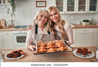 Senior woman and her attractive daughter spending time together at home. Cooking together on kitchen. Happy Mothers' Day.
