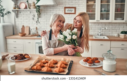 Senior woman and her attractive daughter spending time together at home. Cooking together on kitchen. Happy Mothers' Day. Daughter presenting flowers to her mom.