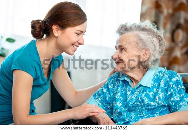 Seniorin mit ihrer Betreuung zu Hause