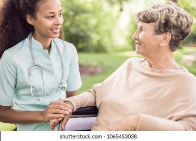 Senior woman and her doctor spending time in the garden outside of the hospital
