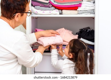 Senior woman with her grandchild storing clothes in wardrobe. Children help grandma by folding laundry. Toddler girl on home study because of Covid 19 outbreak.