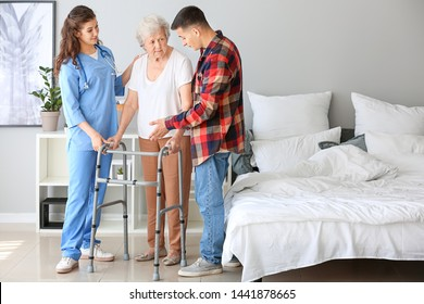 Senior woman with her grandson and caregiver in nursing home