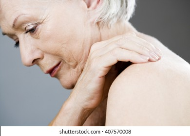 A senior woman with her hand on her shoulder