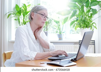 Senior woman in her living room staring annoyed at the screen of her laptop,computer or financial problems