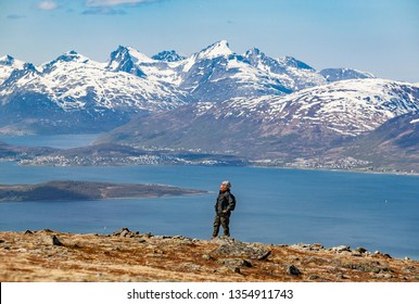 senior woman, hiking above Tromsoe, northern Norway, Scandinavia, view over Tromsoe Fjord and snow covered mountains of early spring