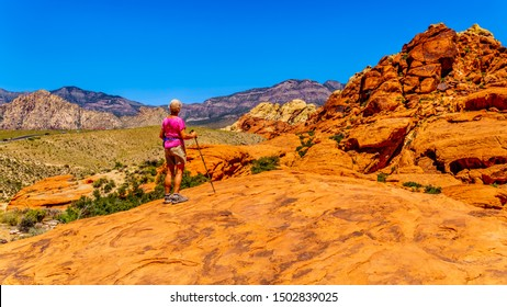 Senior woman hiking on the Red Sandstone Cliffs of the Calico Trail in Red Rock Canyon National Conservation Area near Las Vegas, Nevada, United States