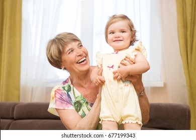 Senior woman hold little baby cute smiling. Happy grandmother with her grandchild in home. Grandmother  playing with their granddaughter.