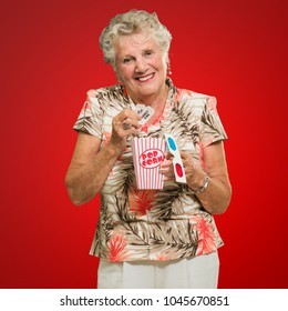 Senior Woman Holding 3d Glasses And Popcorn On Red Background