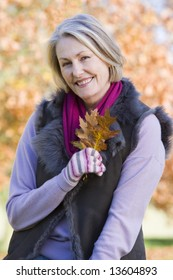 Senior woman holding autumn leaf with trees in background