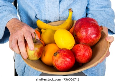 Senior woman holding a basket with fresh and colourful fruits