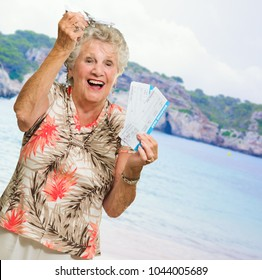 Senior Woman Holding Boarding Pass And Miniature, Outdoors