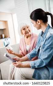 Senior woman holding bottle of pills while young lady using digital tablet for video call with doctor stock photo