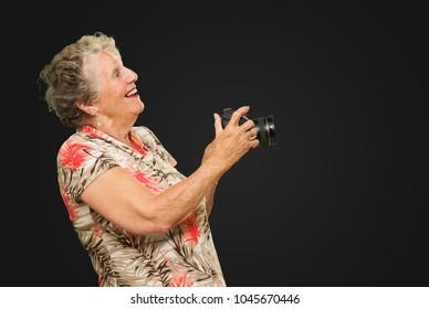 Senior Woman Holding  Camera On Black Background