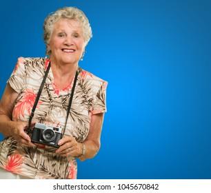 Senior Woman Holding Camera On Blue Background
