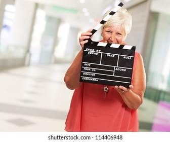 Senior Woman Holding Clapper, Indoor
