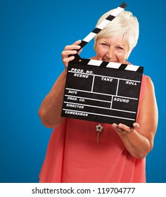 Senior Woman Holding Clapper Isolated On Blue Background
