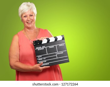Senior Woman Holding Clapper Isolated On green Background