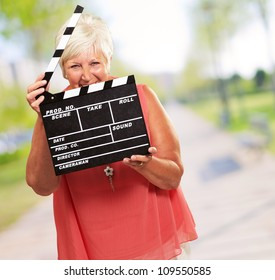 Senior Woman Holding Clapper, Outdoor