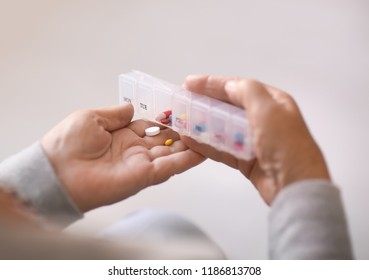 Senior woman holding container with pills, closeup