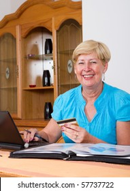 senior woman holding credit card in front of her computer