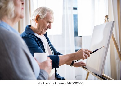 Senior woman holding cup near smiling man painting picture on easel