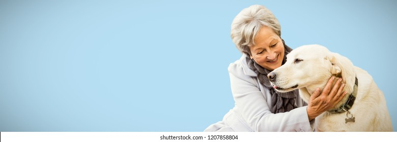 Senior woman holding a dog against blue background