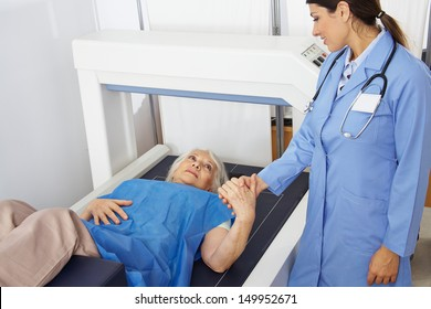Senior woman holding hand of doctor in radiology while getting bone density measurement