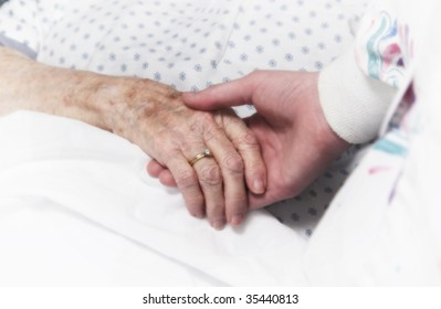 senior woman holding hand of nurse