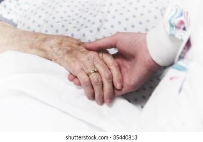 senior woman holding hand of nurse