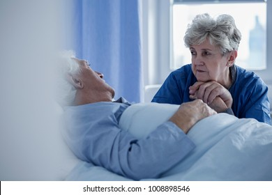 Senior woman holding the hand of a sick man lying in a hospital bed
