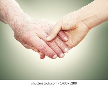 Senior Woman Holding Hands with a Young Lady on a green vintage background
