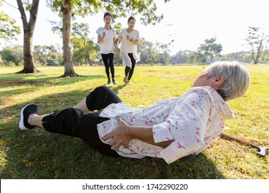 Senior woman is holding her hip,severe pain in her muscle,broken bone,injury to the waist,old elderly lying on the ground,she fell down while strolling,daughter,granddaughter ran to help grandmother
