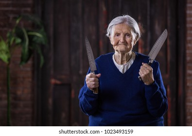 Senior woman holding kitchen knives indoors. Security and self-defense concept. Could be used in humorous way.
