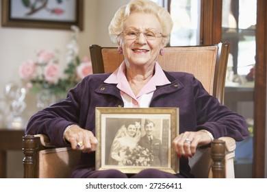 Senior woman holding an old wedding photo