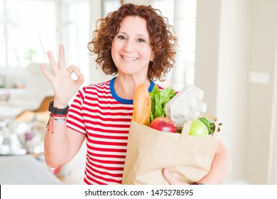 Senior woman holding paper bag full of fresh groceries from the supermarket doing ok sign with fingers, excellent symbol