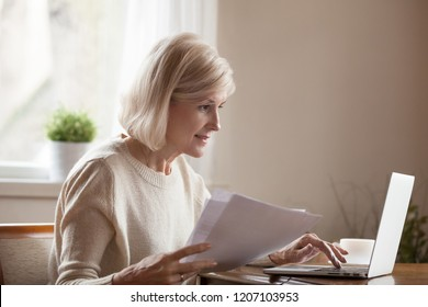 Senior woman holding papers busy at laptop managing house utility bills or finances, aged female using computer working with bank loan or mortgage documents online. Elderly and technology concept