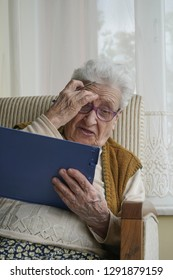 senior woman holding a pen while reading a questionnaire