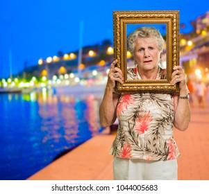 Senior Woman Holding Picture Frame, Outdoors